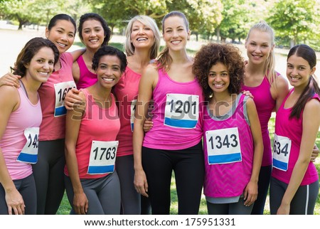 Group of happy women participating in breast cancer marathon standing together park - stock photo