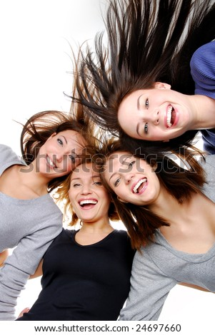 Group of happy women standing in huddle, smiling, low ange view. - stock photo
