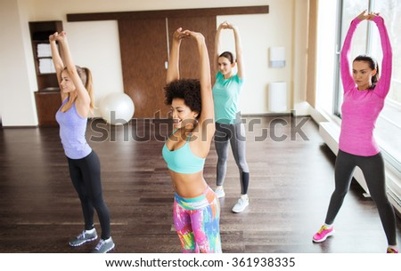 group of happy women working out in gym