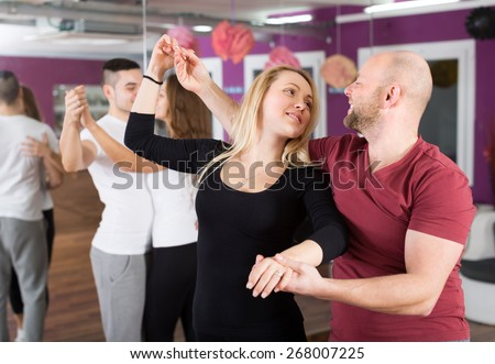 Group of happy young adults dancing salsa in dance club - stock photo