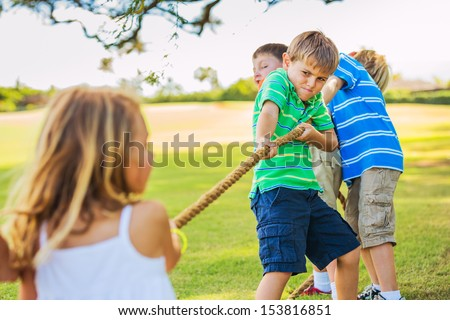 Group of Happy Young Children Playing Tug oF War Outside on Grass - stock photo