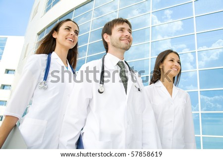 Group of happy young doctors go along a modern building of hospital - stock photo