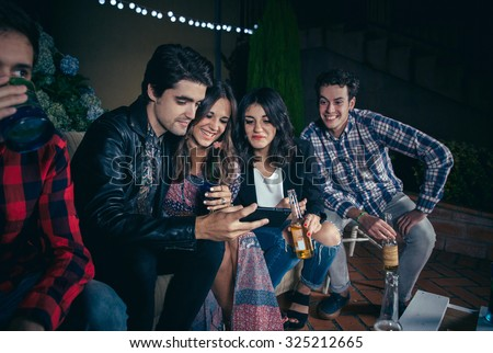 Group of happy young friends drinking and laughing while looking a smartphone picture in a outdoors party. Friendship and celebrations concept. - stock photo