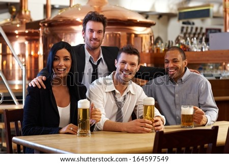 Group of happy young friends drinking beer at pub, smiling. - stock photo