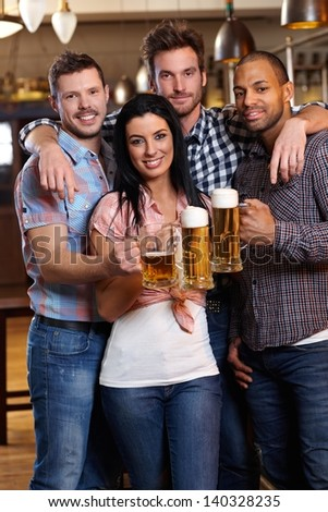 Group of happy young friends drinking beer at pub, smiling, clinking glasses - stock photo