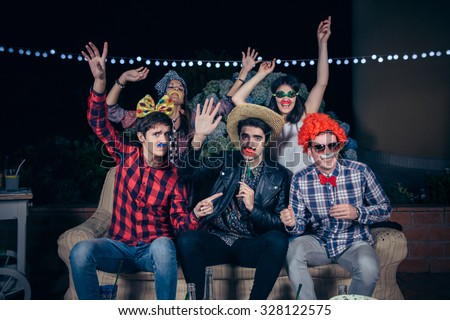 Group of happy young friends having fun with costumes and atrezzo in a outdoors party. Friendship and celebrations concept. - stock photo