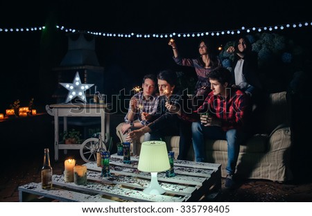 Group of happy young friends holding sparklers and having fun in a outdoors party. Friendship and celebrations concept. - stock photo
