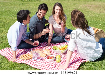 Group Of Happy Young Friends On Vacation Enjoying Wine At Picnic - stock photo