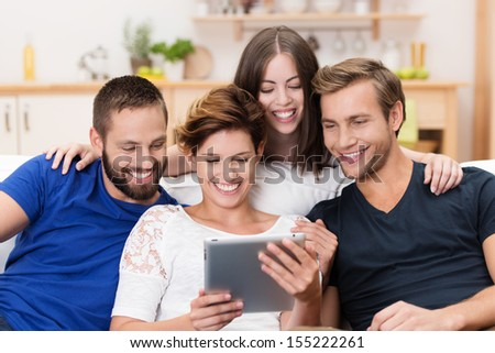 Group of happy young men and women sitting on a sofa together sharing a tablet computer and reading information on the screen - stock photo