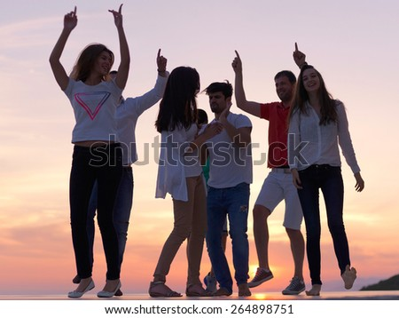 group of happy young people dancing and have fun on party in modern home bacony with sunset and ocean in background - stock photo