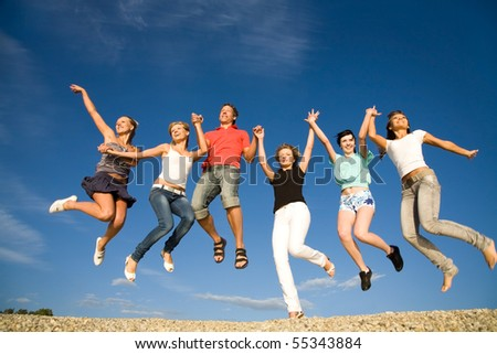 group of happy young people dancing at the beach on  beautiful summer day - stock photo