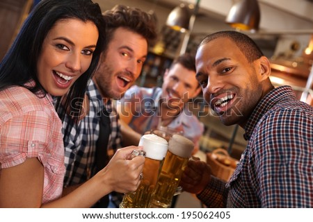Group of happy young people drinking beer, having fun in pub, laughing.