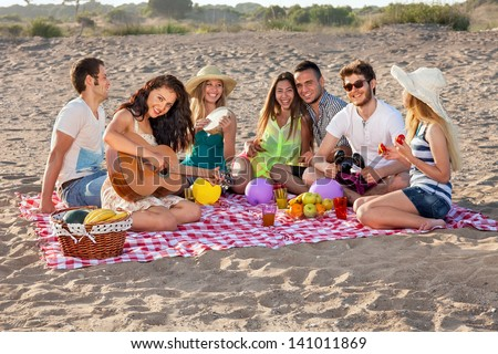 Group of happy young people having a picnic on the beach. Students having an enjoyable picnic on the beach with healthy food, some making music, young female is playing guitar. - stock photo