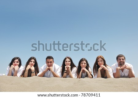 Group of happy young people in circle at beach have fun - stock photo