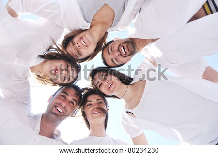 Group of happy young people in circle at beach  have fun and smile - stock photo