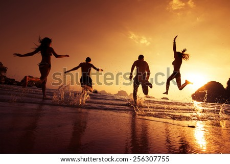 Group of happy young people is running on background of sunset beach and sea - stock photo