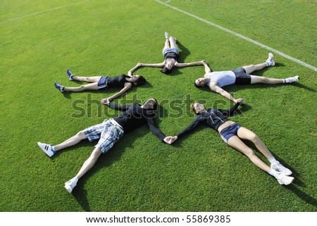 group of happy young people lie on grass outdoor at sunny day - stock photo