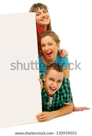 Group of happy young people look out from the blank billboard. Isolated on white background