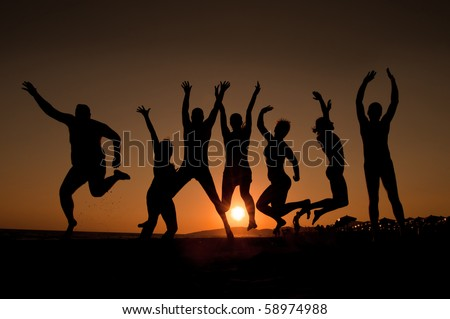 group of happy young people silhouettes jumping on the beach   on beautiful summer sunset