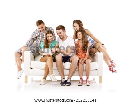 Group of happy young people sitting on sofa and using digital tablet, isolated on white background. Best friends - stock photo
