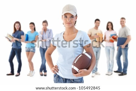 Group of happy young people, smiling woman at front holding football, isolated on white background.