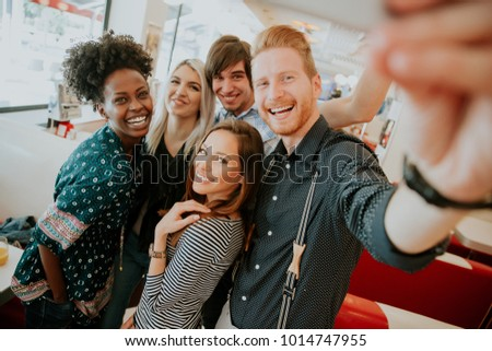 Group of happy young people taking selfie with mobile phone in the diner