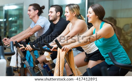 Group of happy young people training on exercise bikes in gym