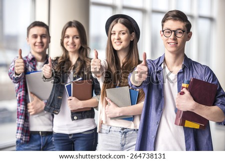 Group of happy young students showing thumbs up in a college. - stock photo