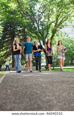 Group of happy young students walking to college - stock photo
