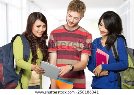 Group of happy young teenager students standing and smiling with books and tablet - stock photo