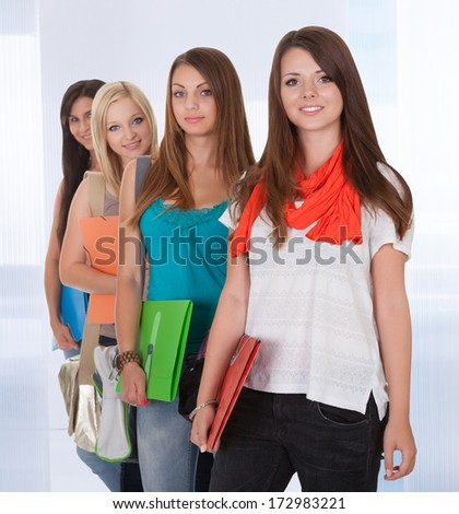 Group Of Happy Young Women Friends Standing In A Row - stock photo