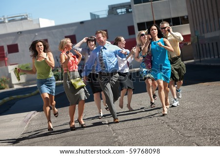 Group of hard working business men and women run down city street. - stock photo
