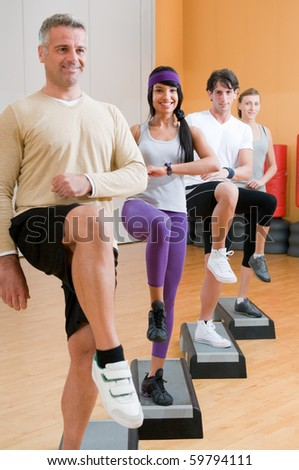 Group of healthy people with instructor doing aerobic exercises with step at gym - stock photo
