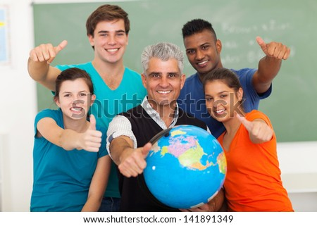 group of  high school geography students and senior teacher giving thumbs up in classroom