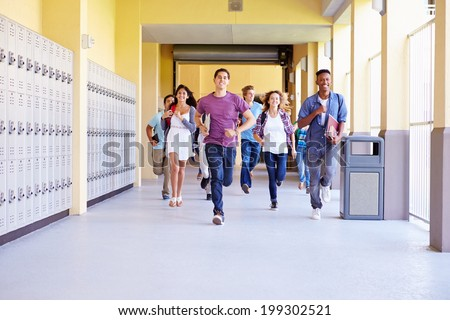 Group Of High School Students Running In Corridor - stock photo