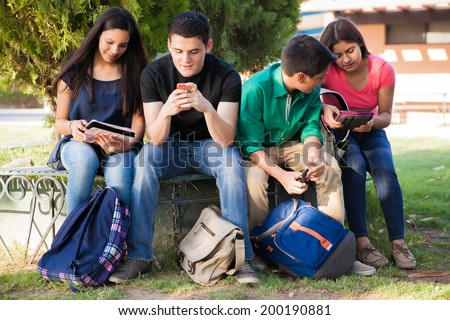 Group of high school students using cell phones and tablets while relaxing outdoors