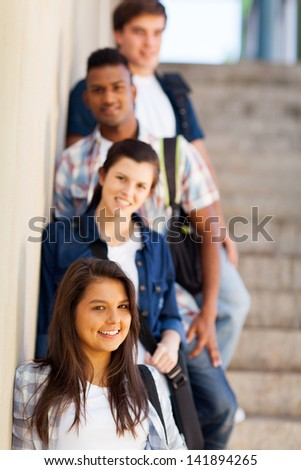group of highschool girls and boys standing by corridor - stock photo