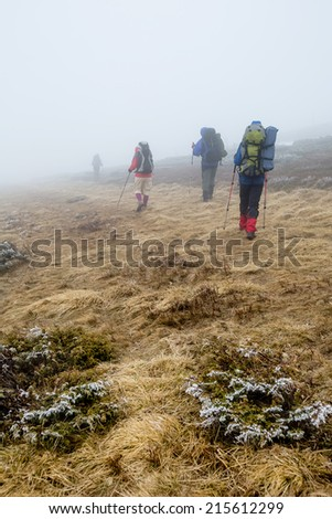 Group of hiker are walking in mountains covered with dense clouds - stock photo