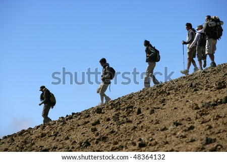 Group of hikers going down a hill - stock photo
