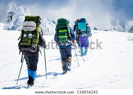 group of hikers in winter mountains - stock photo
