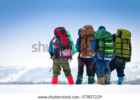group of hikers in winter mountains enjoying a view - stock photo