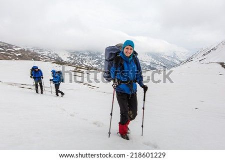 Group of hikers in winter mountains on cloudy day - stock photo