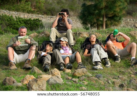 Group of hikers laid in the grass - stock photo