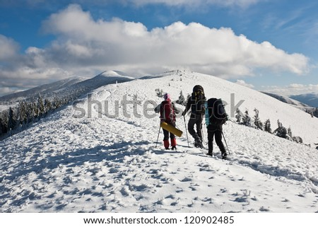 Group of hikers moving to the top in winter mountain. - stock photo