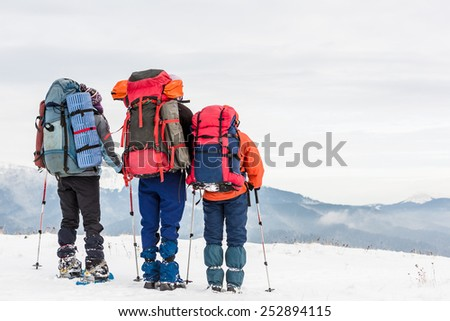 group of hikers relaxing on top in winter mountains - stock photo