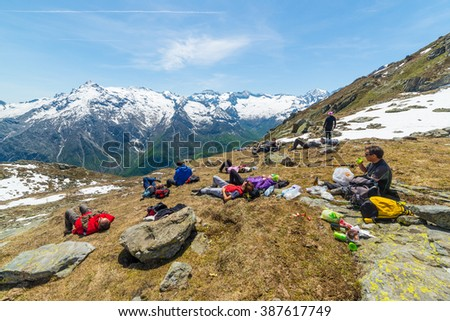 Group of hikers resting on mountain summit with expansive view over the Alps, Courmayeur, Italy. Outdoor activities and wanderlust in summer - spring.