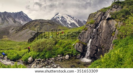 Group of hikers traveling along the green valley in Altai mountains - stock photo