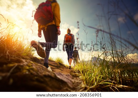 Group of hikers walking in mountains. Edges of the image are blurred - stock photo