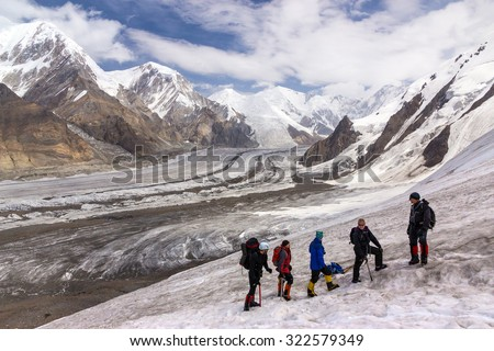 Group of Hikers Walking on Snow and Ice Terrain. Large Group of People Sport Clothing Climbing Gear High Altitude Boots Going Up Mountain Peaks Sunlight Cloud Sky Massive Glacier Flow on Background - stock photo