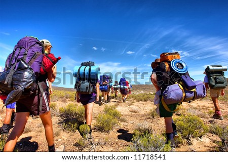 Group of hikers walks in savanna - low-angle view. Shot in the Langeberge highlands near Grootrivier and Gouritsrivier rivers crossing, Garden Route, Western Cape, South Africa. - stock photo